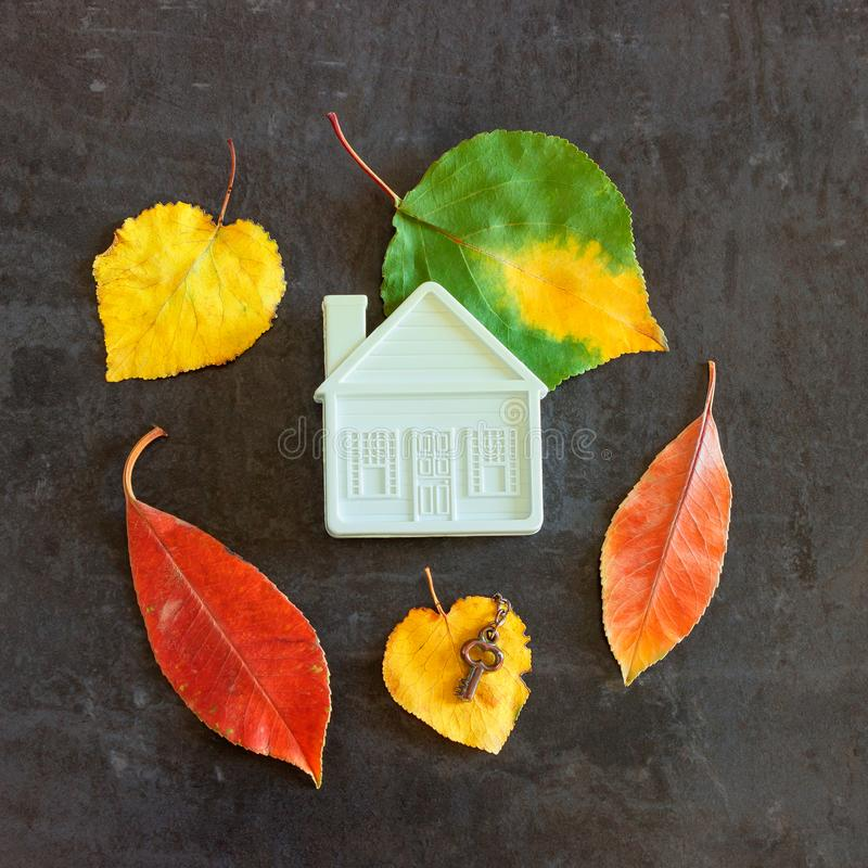在五颜六色的秋叶中的小玩具房子 免版税库存照片