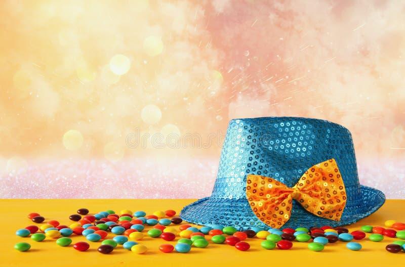 在五颜六色的糖果旁边的蓝色发光的党帽子 图库摄影