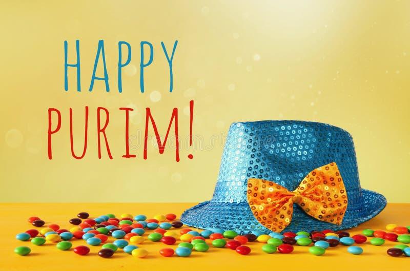 在五颜六色的糖果旁边的蓝色发光的党帽子 库存照片
