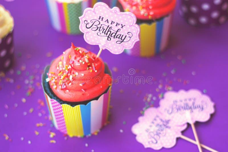 在五颜六色的纸烘烤的杯子的鲜美草莓杯形蛋糕,有生日快乐贺卡的,在黄色背景 党后面 库存照片