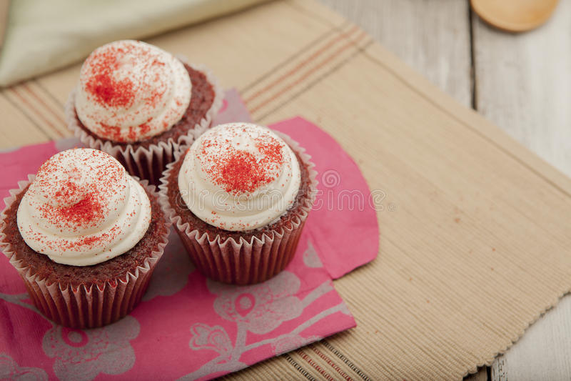 在五颜六色的纸袋的三块红色天鹅绒杯形蛋糕 免版税库存照片