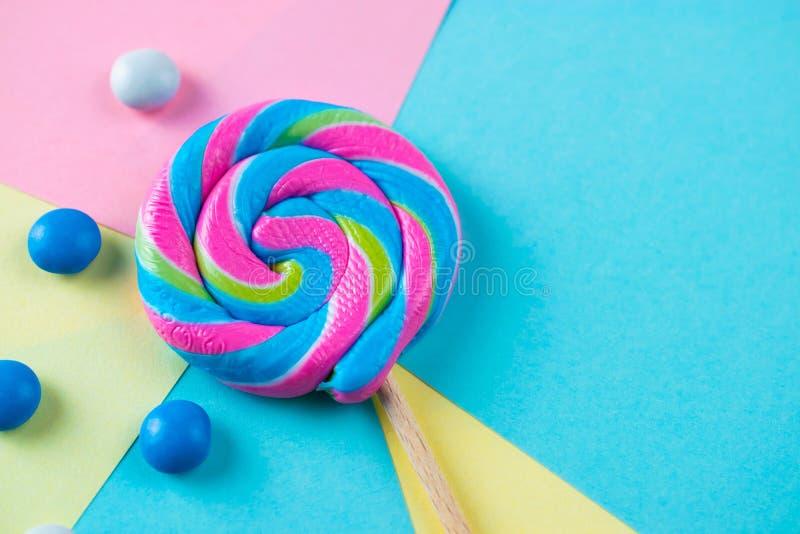 在五颜六色的背景,平的被放置的射击的明亮的棒棒糖糖果 库存图片