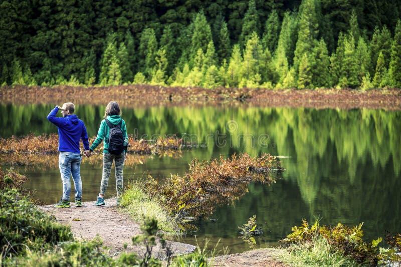 在五颜六色的运动衫的年轻夫妇在火山的湖前面站立 免版税图库摄影