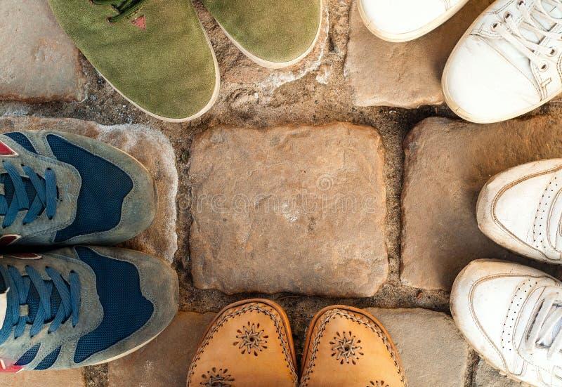 在五颜六色的运动鞋的许多脚在石头的圈子,体育概念,拷贝空间站立 免版税库存照片