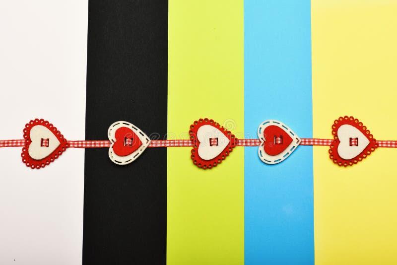 在五颜六色的镶边背景的手工制造装饰 与红色和白色心脏的被检查的丝带成了串珠状对此 华伦泰 免版税库存图片
