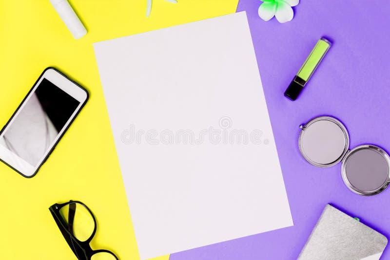 在五颜六色的黄色和紫色背景的白色A4空白框架与智能手机,镜子,唇膏,玻璃,笔记薄 库存照片