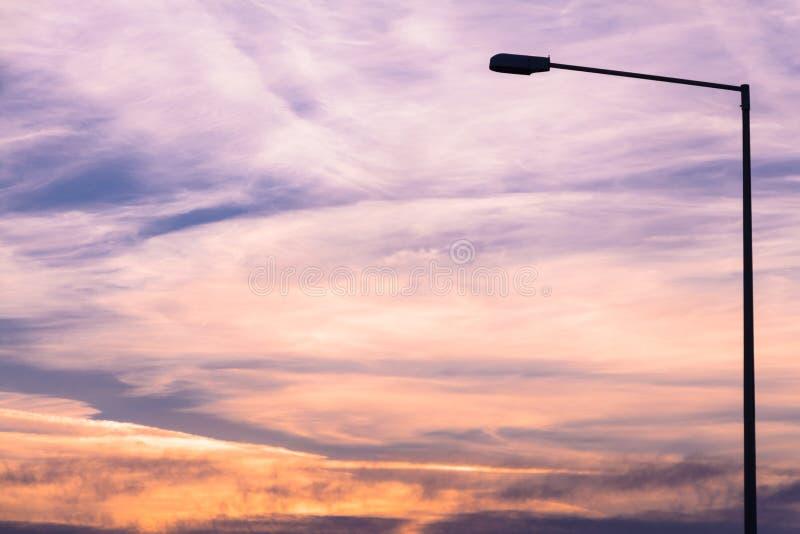 在五颜六色的黎明/黄昏天空背景的街灯剪影 库存照片