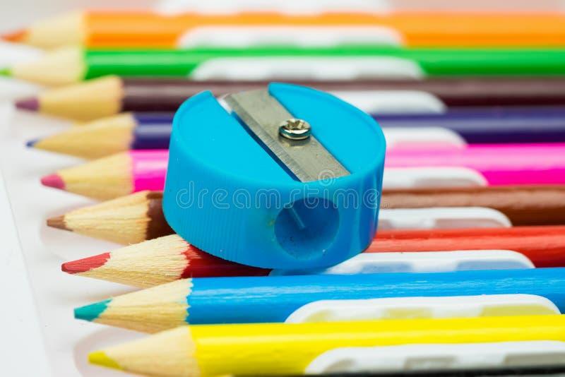 在五颜六色的pPencil磨削器的铅笔刀在五颜六色的铅笔背景 学校stationeencils背景 教育文教用品 免版税库存照片