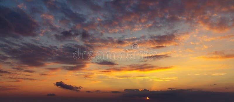 在五颜六色,明亮的橙色日落,太阳的光芒期间的天空通过云彩做他们的方式 库存图片