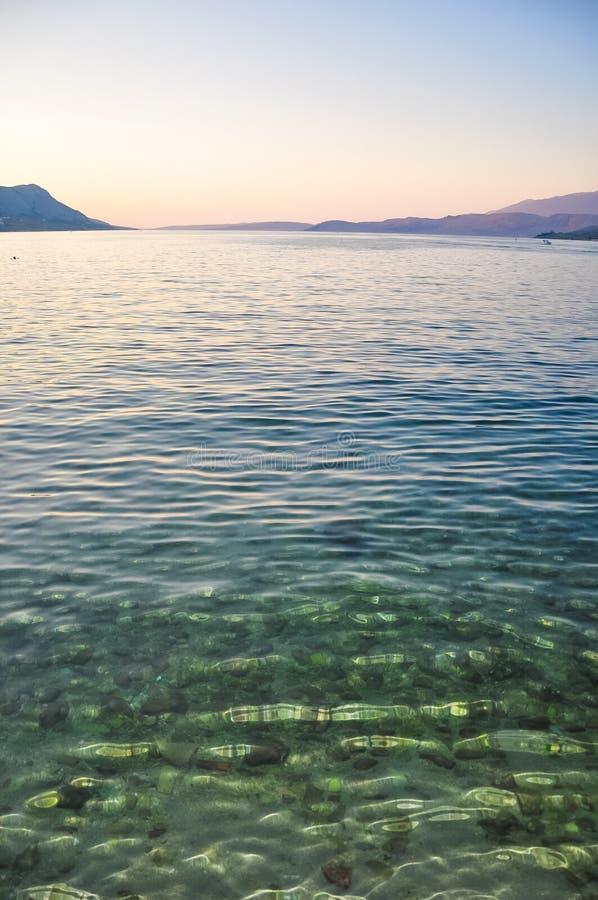 在亚得里亚海海岛Pag,在日落以后的克罗地亚海岸的透明的水  免版税图库摄影
