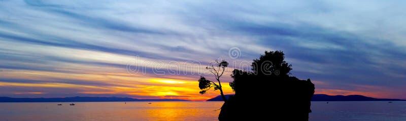 在亚得里亚海的剧烈的日落和卡梅尼火山Brela -小著名海岛在Brela 免版税库存图片