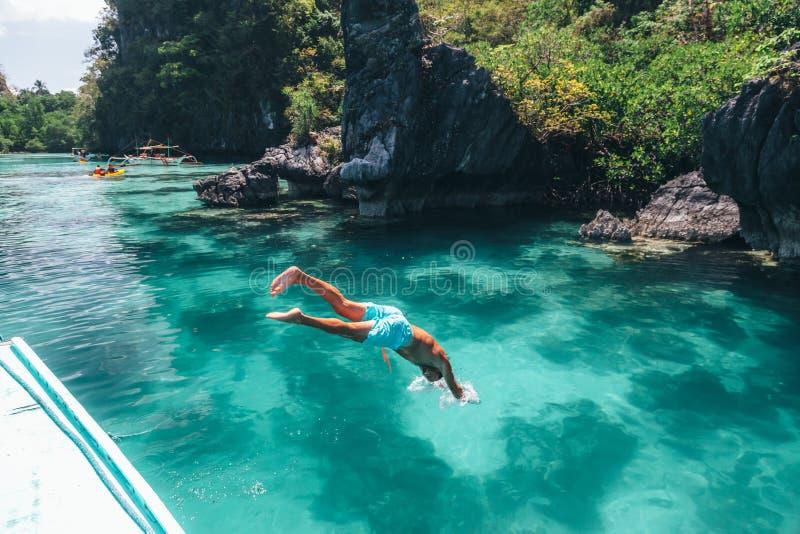 在亚洲供以人员跳进清楚的海水 免版税图库摄影