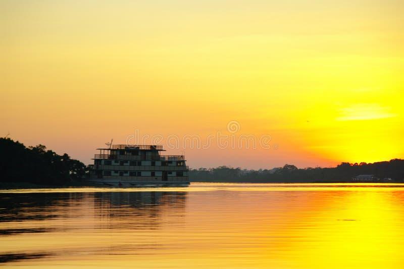 在亚马孙河的巡航小船日落的 库存图片