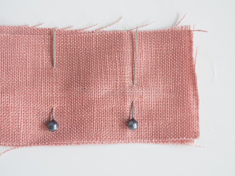 在亚麻制织品的缝合的别针在白色背景,一起附有的织品缝合的别针用途临时地在缝合它前与 库存照片