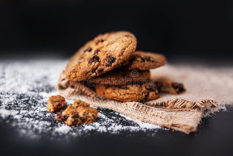 在亚麻布餐巾的巧克力曲奇饼在黑背景 巧克力 库存图片