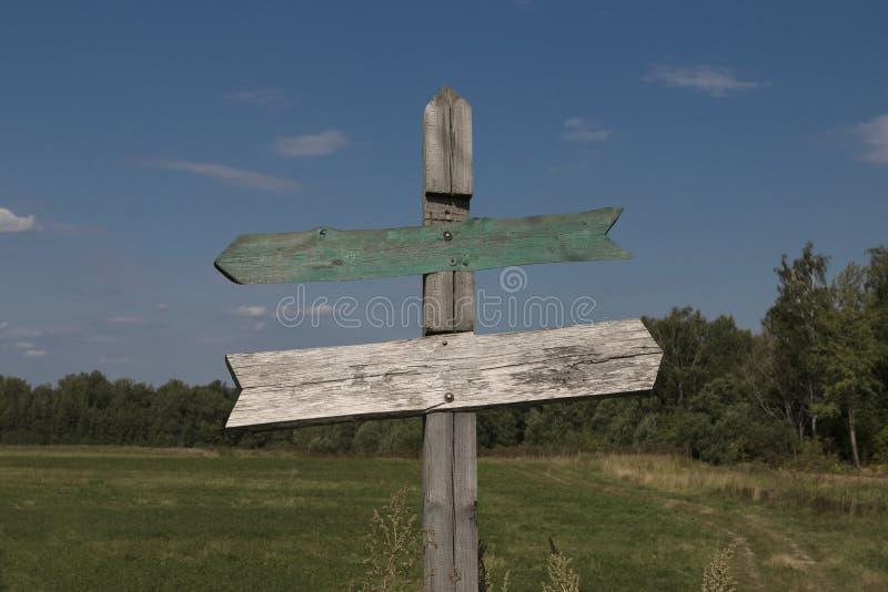 在交叉路的木路标有两个箭头的 免版税图库摄影