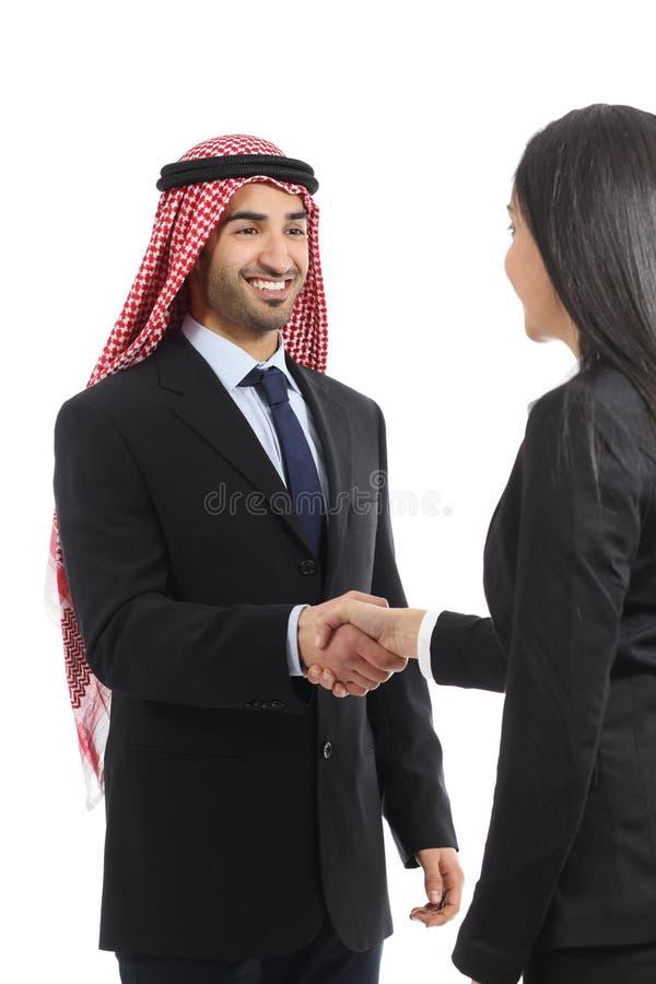 在交涉的阿拉伯沙特愉快的商人握手 免版税库存图片