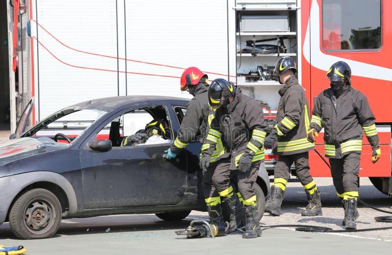 在交通事故期间的消防队员 免版税库存照片