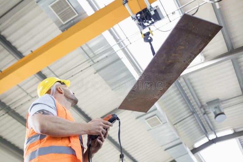 在产业的体力工人运行的起重机举的金属板低角度视图  免版税库存照片