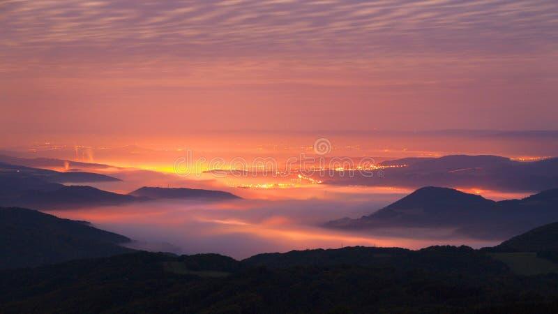 在产业镇上的秋天日出在波希米亚。从有雾的背景增加的小山峰顶。 库存图片