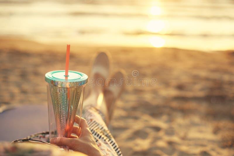 在享受与鸡尾酒的妇女的后面看法日落在阿尔巴尼亚在亚得里亚海含沙海岸 免版税库存照片