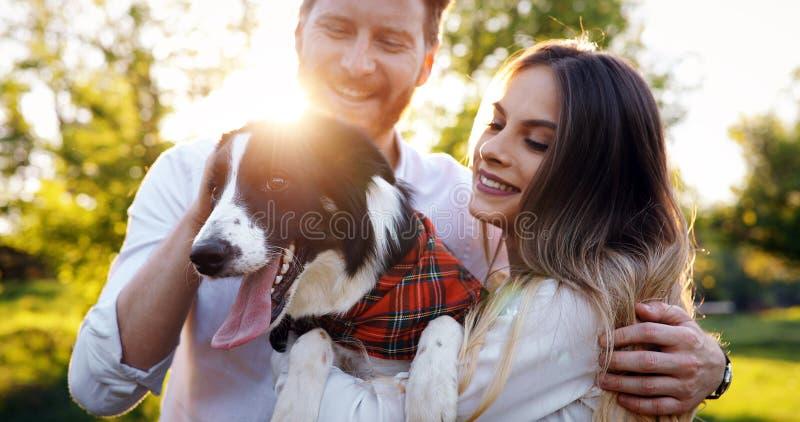 在享受他们的与宠物的爱的浪漫愉快的夫妇时间 免版税库存图片
