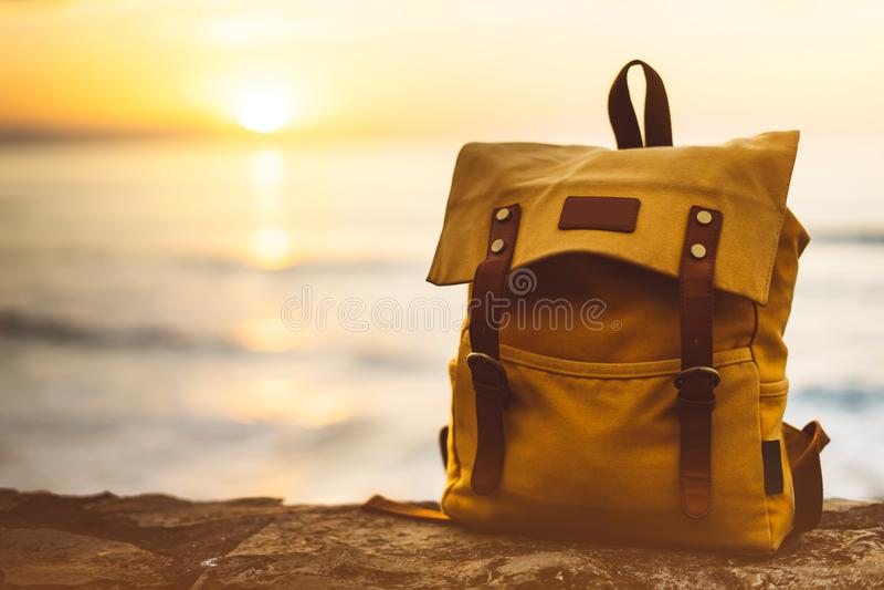 在享受日落海洋天际,被弄脏的全景海景太阳的背景蓝色海的行家远足者旅游黄色背包特写镜头 免版税库存图片