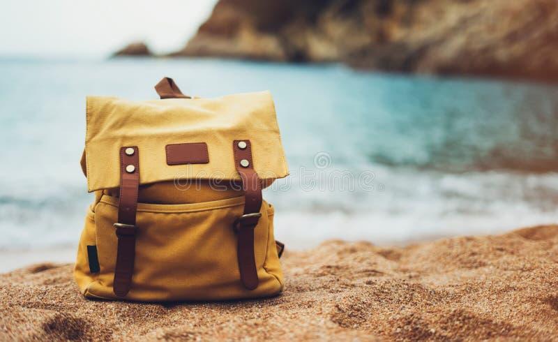 在享受日落海洋天际,被弄脏的全景海景太阳的背景蓝色海的行家远足者旅游黄色背包特写镜头 免版税库存照片