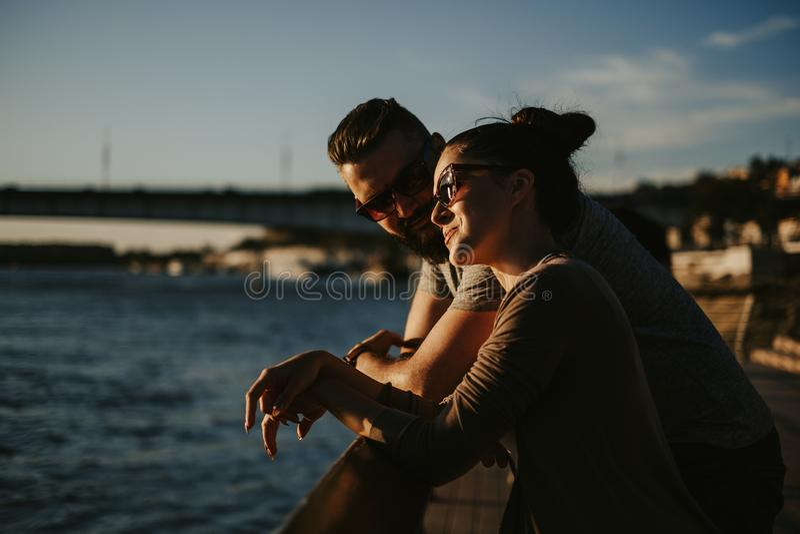 在享受日落的爱的夫妇由河 免版税库存照片