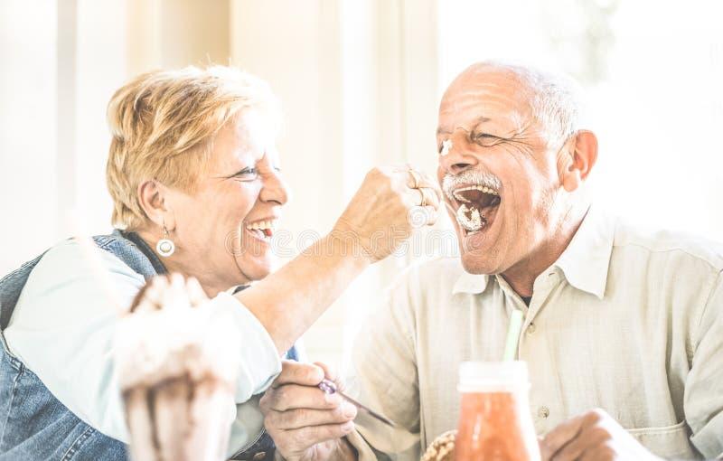 在享用生物冰淇凌杯子的爱的愉快的退休的资深夫妇 图库摄影