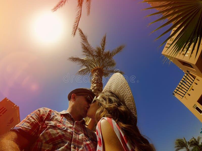 在亲吻在棕榈树背景的爱的年轻夫妇 免版税库存图片
