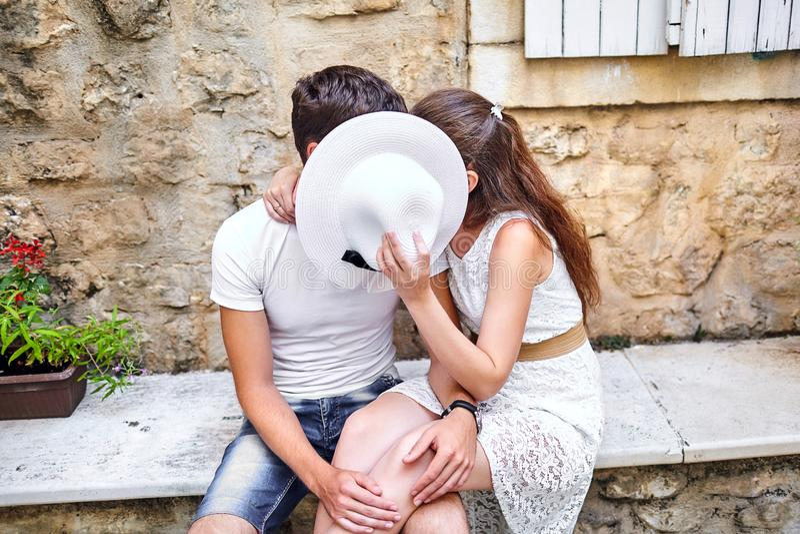 在亲吻在石benc的白色女性帽子后的爱的夫妇 免版税库存图片