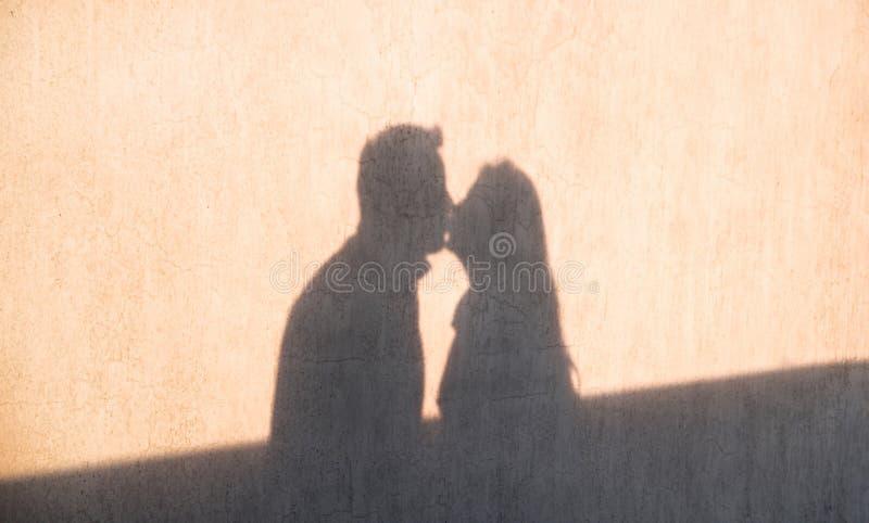 在亲吻的爱恋的夫妇墙壁上的阴影  免版税库存照片