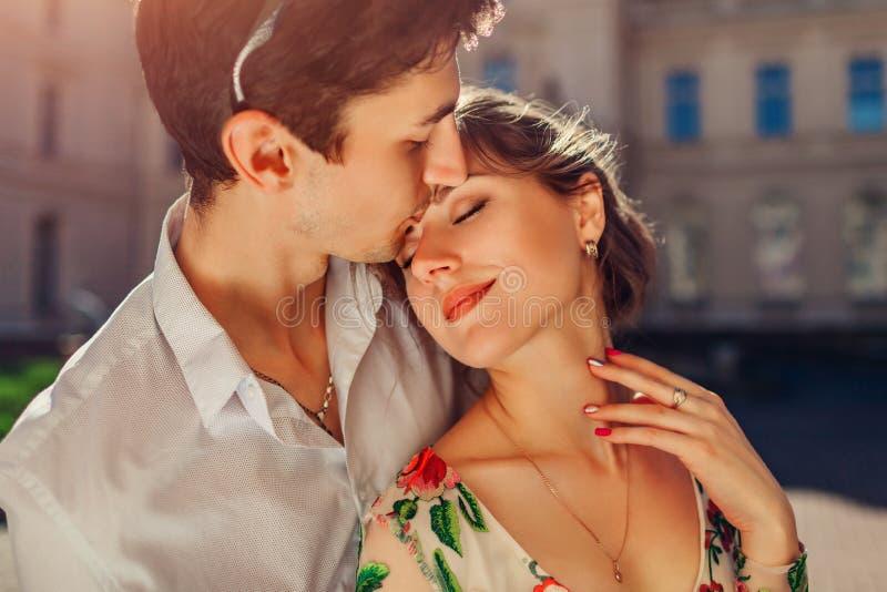 在亲吻的爱的年轻愉快的夫妇拥抱和户外 走由Potocki宫殿的男人和妇女在利沃夫州 免版税库存照片