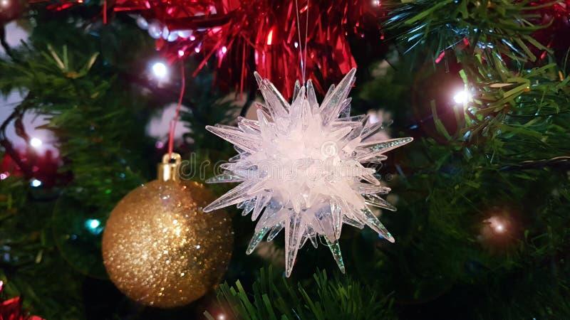 在人为圣诞树的中间的特写镜头与美丽的圣诞节装饰品的与金黄圆球和白色星 免版税库存图片