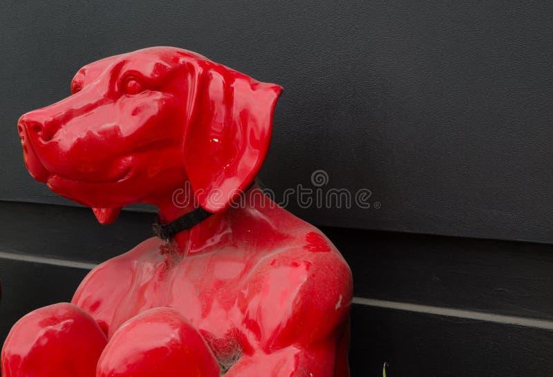 在人体的红色狗雕刻坐,是艺术品显示由侍从和Marc画廊 免版税库存图片