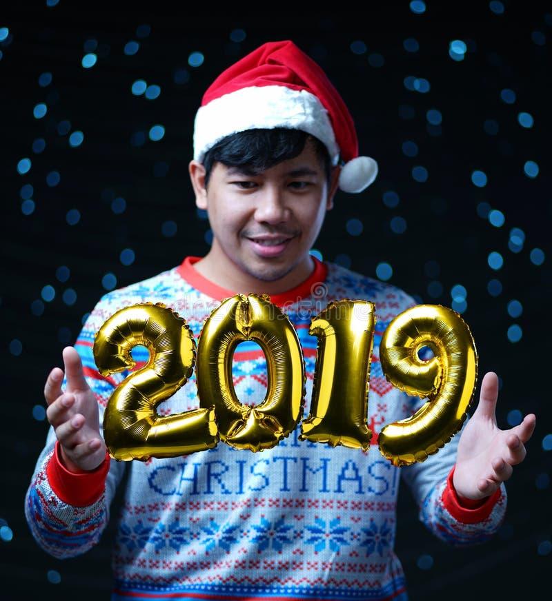 2019在人佩带的圣诞节服装附近的金黄气球飞行 免版税库存照片