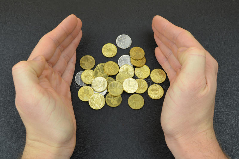 在人手之间的硬币在黑背景 古铜色硬币 图库摄影