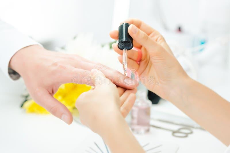 在人手指甲的修指甲师倾吐的油在修指甲以后的 免版税库存照片