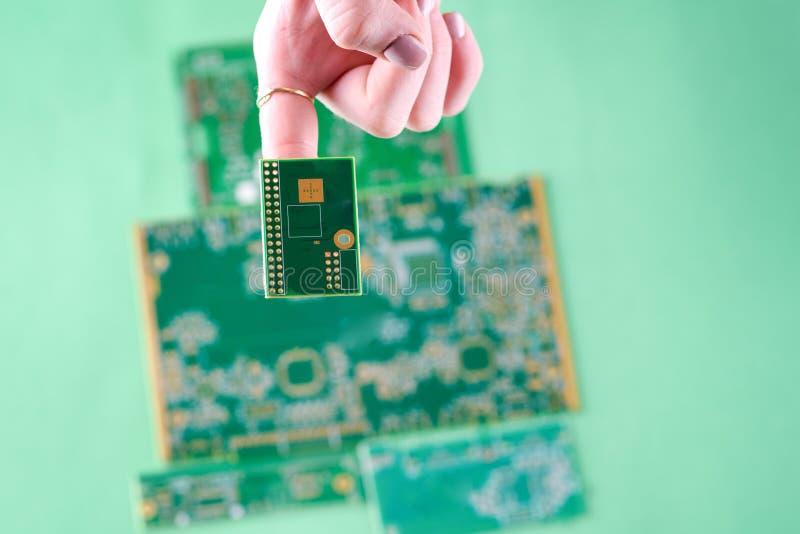 在人的妇女手指的小电子电路板 库存照片
