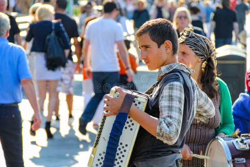 在人群街道上的一部年轻卖艺人执行的手风琴在南B 库存图片