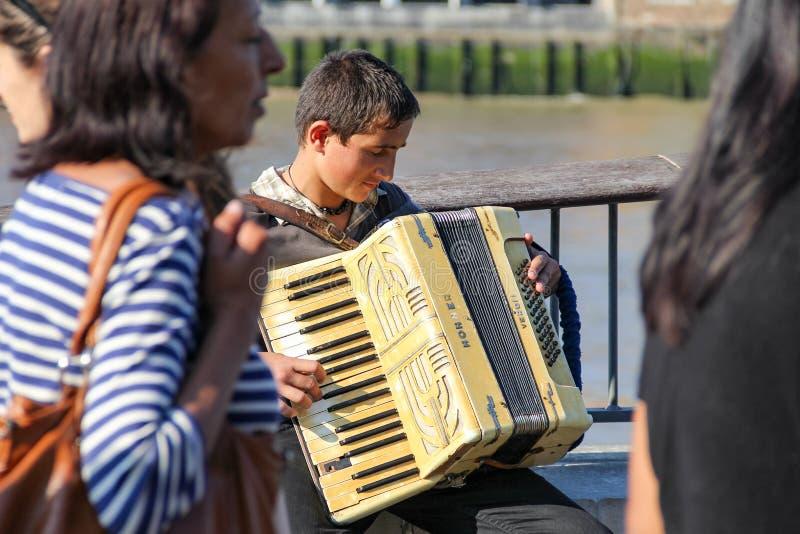在人群街道上的一部年轻卖艺人执行的手风琴在南B 免版税库存图片