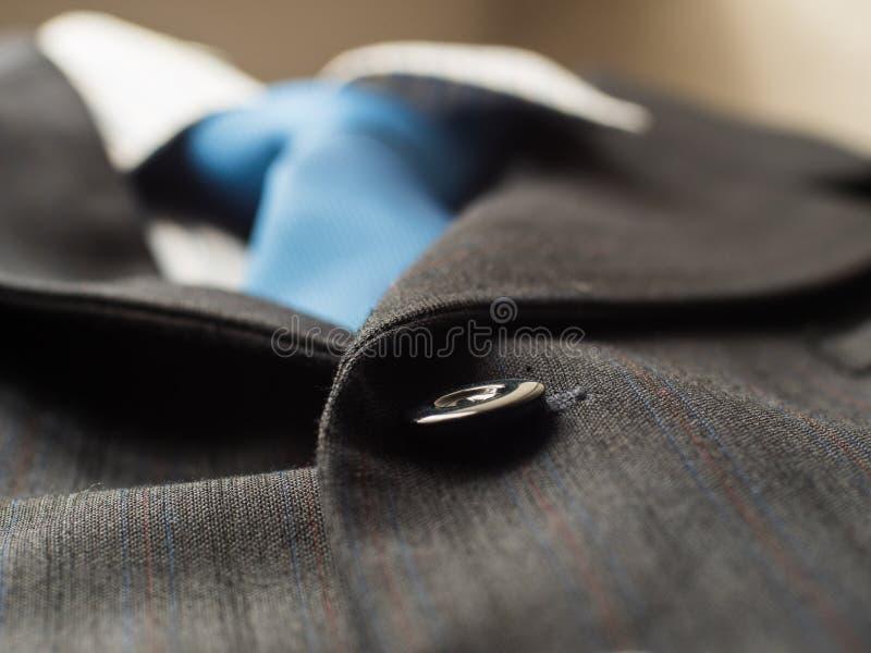 在人` s的黑按钮适合与蓝色领带的背景,关闭 库存图片