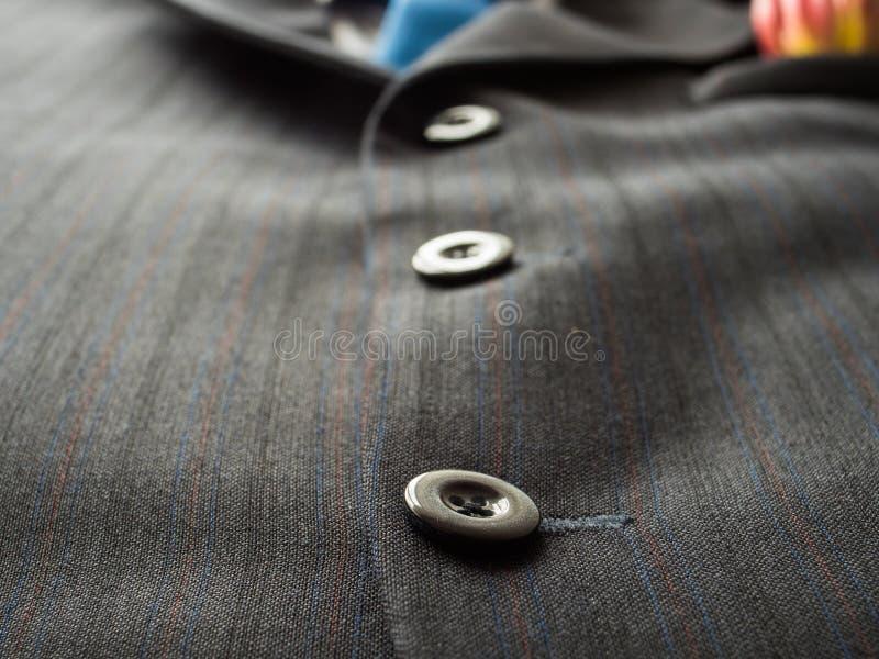 在人` s的黑按钮适合与蓝色领带的背景 ,接近 免版税库存图片
