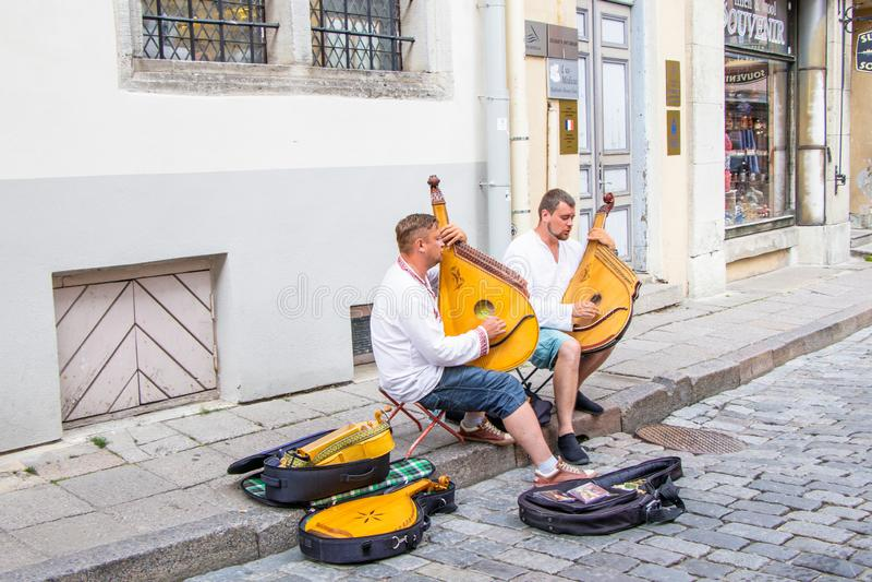 在从乌克兰的塔林艺术家老城市的街道上唱一首民歌对风笛的陪同 免版税图库摄影
