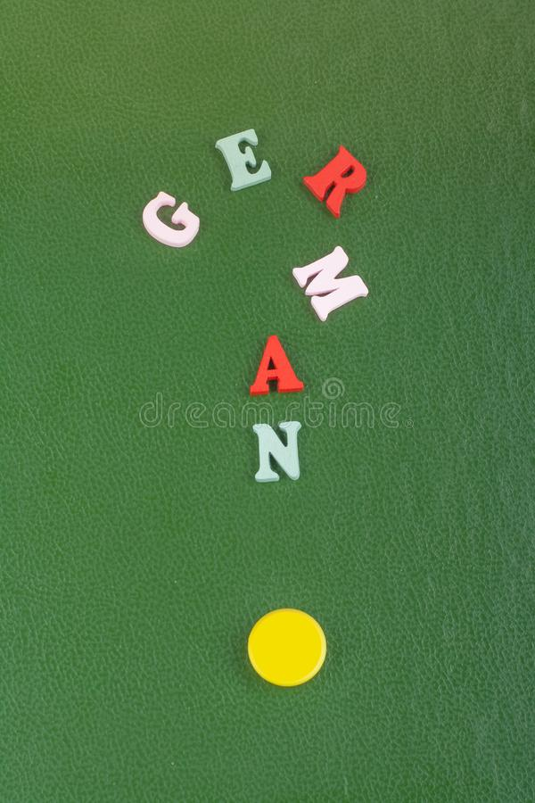 在从五颜六色的abc字母表块木信件组成的绿色背景,广告文本的拷贝空间的德国词 库存图片