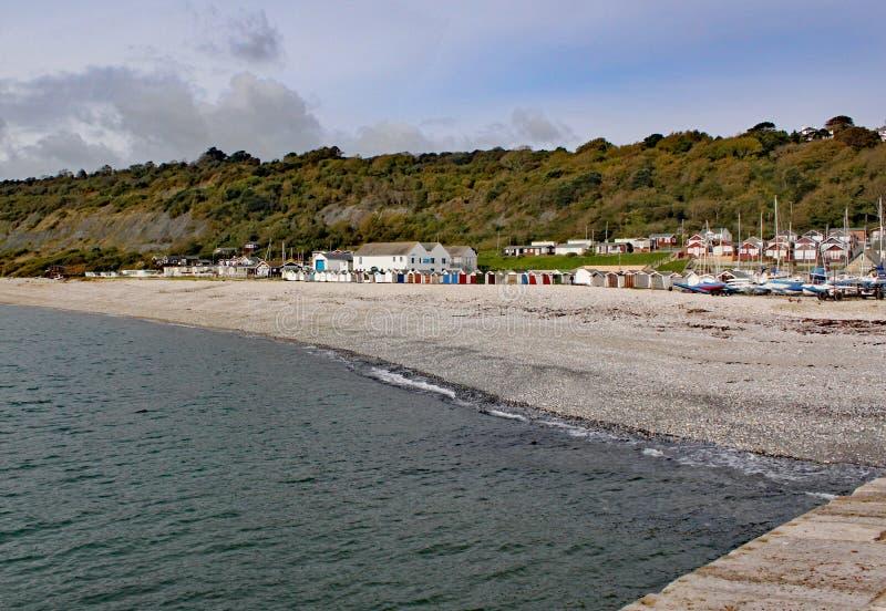 在从科布观看的木瓦海滩的海滩小屋在莱姆里杰斯,多西特,英国 免版税库存图片