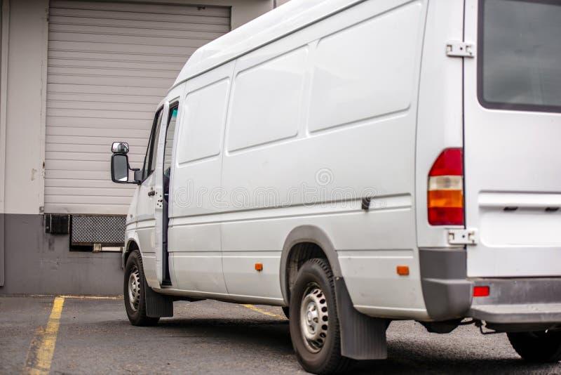 在仓库坞门的紧凑微型搬运车身分交付的拾起货物的 库存图片