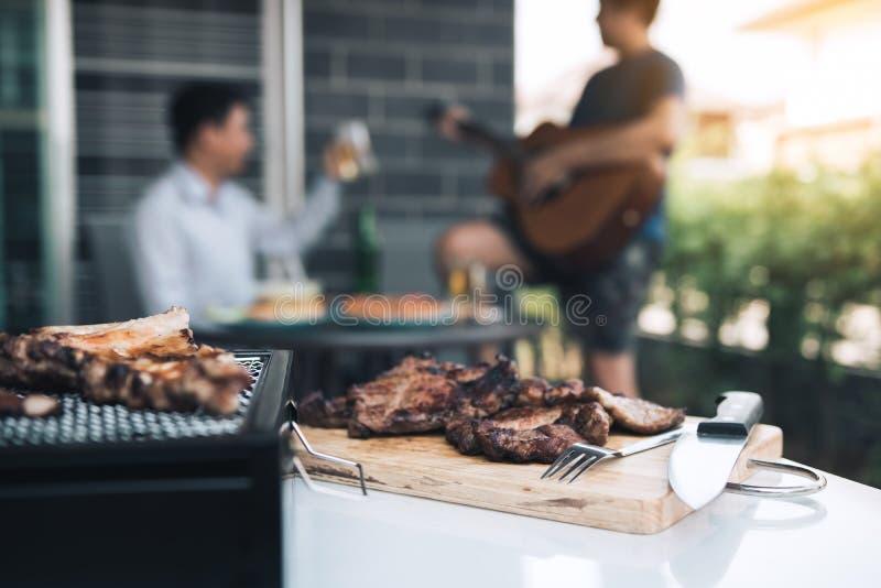 在他们弹吉他并且一起唱歌烤肉和各种各样的食物的朋友的关闭在格栅和庆祝 免版税库存照片