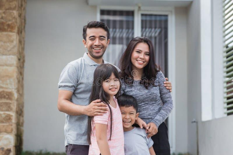 在他们的房子前面的愉快的亚洲家庭 库存图片